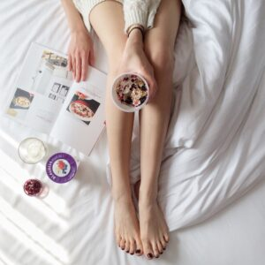 Lady holding a cup of yogurt above her legs while sitting on a bed looking at a cookbook