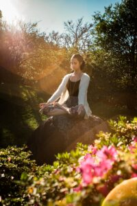 Woman,sitting peacefully on a rock,meditating out in nature with the sun shining on her